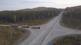 Truck car with freight container driving on cross roads at highway. Aerial view three truck cars with freight container driving on highway road on background stock video footage