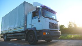 Truck with cargo trailer riding on road and transporting goods at sunset time. Lorry riding through countryside among stock video footage