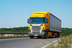 The truck carries cargo on the highway in the tilt van. Front vi. Cargo truck with tilt van transporting goods on highway. Front view. Wide angle Royalty Free Stock Photo