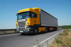 The truck carries cargo on the highway in the tilt van. Front vi. Ew. Blurred in motion Stock Photos