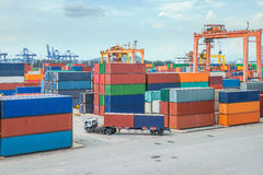 Truck carries container to a warehouse in dock.  Stock Photos