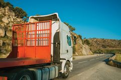 Truck carrying another truck by road on hilly landscape stock image