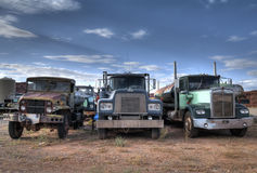 Truck cemetary. Junkyard with three trucks standing in the foreground royalty free stock photos
