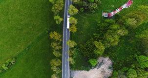 Truck on a cinematic road aerial shot 4K. 4K Following a truck on a cinematic road aerial shot Delivering goods - Supply Chain stock video footage