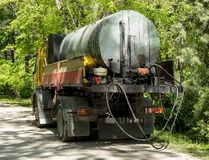 A truck with a cistern for transporting tar or bitumen on the side of a road in a public park. Repair of asphalt roads. Asphalt. Paving and urban improvement stock photo
