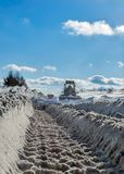 Truck cleaning road in winter. Machinery with snowplough cleaning road by removing snow from intercity highway after winter blizzard Royalty Free Stock Image