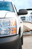 Truck closeup with fishing boat in background. White truck closeup with a fishing boat on a boat trailer in the backgrund that's being pulled by the truck stock images