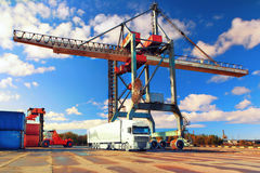 Truck container truck and crane in the port. Loading and unloading of containers crane truck and special truck in the port on a sunny day Royalty Free Stock Photos