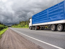 Truck on country highway and stormy clouds. Truck on highway goes to storm Stock Photos