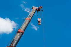 Truck crane boom with hooks and scale weight above blue sky Stock Photography