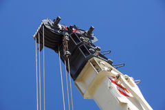 Truck crane detail boom with hooks and scale weight above blue sky Stock Photography