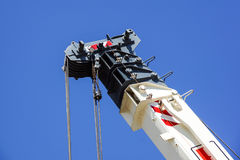 Truck crane detail boom with hooks and scale weight above blue sky Royalty Free Stock Photo