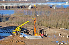 Truck crane and pile driver during construction works at the building site Stock Images