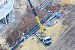 Truck Crane puts underground pipes at construction site. Stock Image
