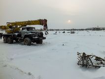 The truck crane in the snow in the field. Mobile crane in the snow-covered field Royalty Free Stock Images