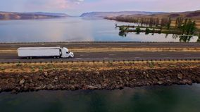 Truck crossing Columbia river with canyons in background. Sweeping aerial of a semi truck crossing the Columbia river with canyon hills in background on a bright stock video footage