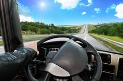 Truck dashboard with driver`s hand on the steering wheel on the. Countryside road against blue sky with sun royalty free stock photos
