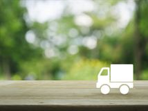 Business transportation truck concept. Truck delivery icon on wooden table over blur green tree background, Transportation business concept stock photos