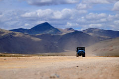 Truck through the desolate deserts high mountains. Royalty Free Stock Image