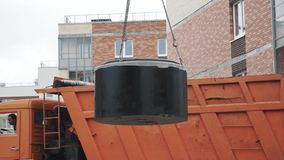 Truck drive at building site with concrete manhole ring swinging on chains. Orange truck drive at building site with concrete chamber manhole ring swinging on stock video footage