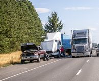 Truck driver changes punctured wheel of the big rig semi truck on the shoulder side of highway next to trucks and cars passing by. Truck driver changes punctured royalty free stock images