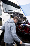 Truck driver checking operation engine semi truck with open hood Royalty Free Stock Image