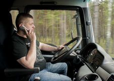 Truck driver driving and talking to phone Royalty Free Stock Photography