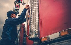 Truck Driver Getting Into Truck. Transportation Industry Theme. Truck Driver Getting Into Truck Time To Hit the Road with Heavy Load stock photos