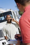 Truck Driver With His Coworker. An African American truck driver looking at coworker while using cell phone Royalty Free Stock Photos