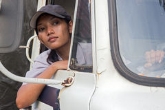 Truck driver looking out the open window. Woman truck driver in the car Stock Photos