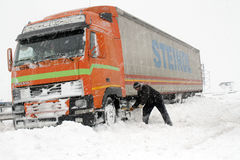 Truck driver shovels snow to free his truck Royalty Free Stock Images