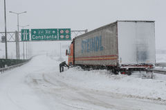 Truck driver shovels snow to free his truck Stock Photography