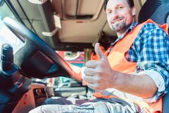 Truck driver sitting in cabin giving thumbs-up. Truck driver man sitting in cabin giving thumbs-up royalty free stock photography
