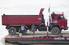 Truck with drivers on a barge pulled by a motorboat in Bolivia. Closeup on truck with drivers on a barge pulled by a motorboat on the river beni in Bolivian stock photography