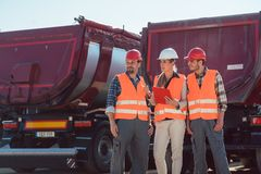 Truck drivers and dispatcher in front of lorries in freight forwarding company. Truck drivers and dispatcher talking in front of lorries in freight forwarding royalty free stock photo