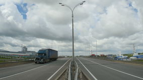 Truck Drives along Highway Industrial Buildings on Sides. KAZAN, TATARSTAN/RUSSIA - JUNE 08 2015: Truck and car approach camera driving along highway big colored stock footage