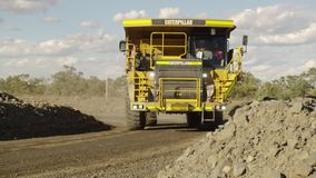 A truck drives past a dirt road. A steady shot of a dirt road as a yellow truck drives past by it stock video
