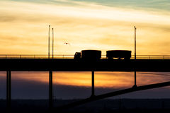 Truck driving on a bridge on a background of a beautiful sky. Cargo car goes over the bridge on the background of the beautiful sky. Bridge over river, nature Stock Photo