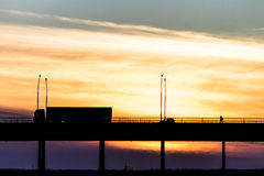 Truck driving on a bridge on a background of a beautiful sky. Cargo car goes over the bridge on the background of the beautiful sky. Bridge over river, nature Royalty Free Stock Images