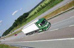 Truck driving on country road. Green white truck speeding on highway surrounded by forrest and fields Stock Image