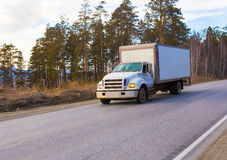 Truck driving on country road. In forest Stock Photos