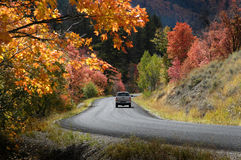 Truck Driving Down Country Roadway in Fall Autumn. Truck driving down country road roadway in fall autumn Stock Image