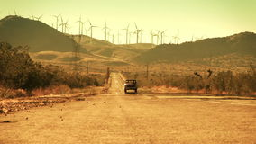 Truck Driving Down Desert Road from Wind Farm. Long shot of an old truck driving down a hot desert road with wind turbines on the mountains in the background stock footage