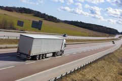 Truck driving into far distance. Grey lorry driving away on motorway Royalty Free Stock Images