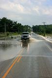 Truck Driving on Flooded Road. A truck makes it safely through a flooded roadway Stock Images