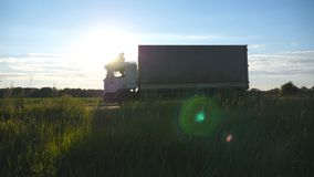 Truck driving on a highway with sun flare at background. Lorry rides through the countryside with beautiful landscape