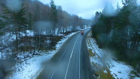 Truck driving on a mountain road in the rain. Aero stock footage