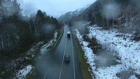 Truck driving on a mountain road in the rain. Aero stock video