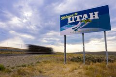 Truck driving past Welcome to Utah sign. Evanston, Utah, United States - August 15, 2018: Shot of a truck driving by the Welcome to Utah sign located on the stock photography