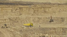 Truck driving in quarry. Small figures of people at the top of the quarry. An excavator stock footage